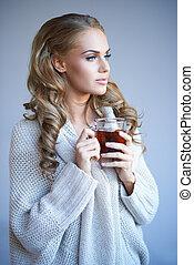 Daydreaming woman drinking tea