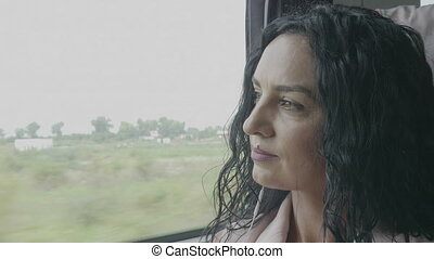Daydreaming young woman enjoying voyage looking outside of the train window relaxing and listening to music on smartphone wearing earphones