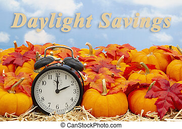 Daylight Savings time change message with a retro alarm clock with pumpkins and fall leaves