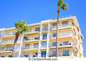 Daylight sunny view to city yellow hotel balconies on palm...