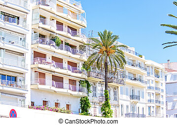 Daylight view from bottom to hotel balconies, palm trees and...