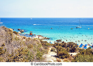 Daylight view from top to Konnos beach with people relaxing