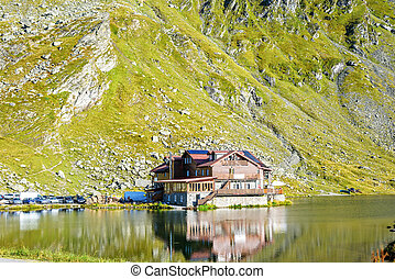 Daylight view to Balea Lake cottage with green mountains