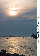 Boats heading in with setting sun and approaching storm