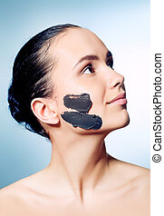 dayspa - Portrait of a woman with spa mud mask on her face.