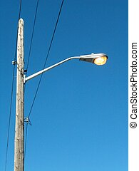 Street lamp shining during the day.