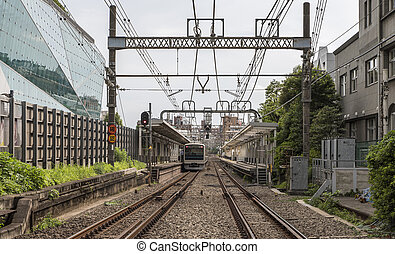 Daytime view along a train track in Tokyo, Japan, with a local train visible in the station