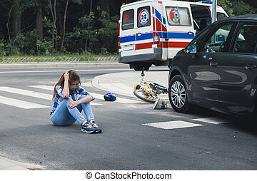 Dazed victim of a car crash sitting on the road with...