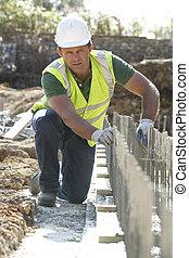 de arbeider van de bouw, het leggen, stichtingen