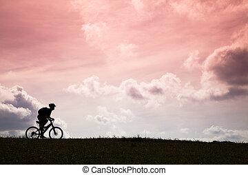 de fiets van de berg, silhouette, ondergaande zon , passagier