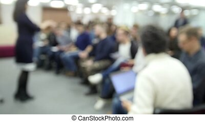 De-focused - a lot of people sitting at a seminar or...
