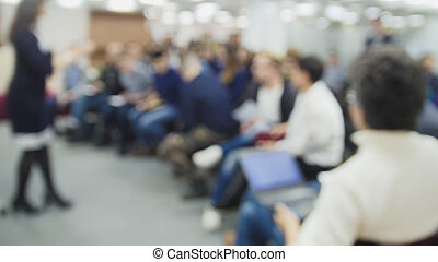 De-focused presentation - a lot of people sitting at a seminar or lectures - background