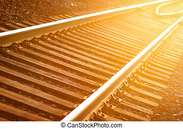 De focused curved railroad tracks in sunset, travel background