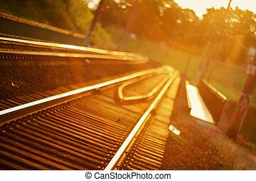 De focused curved railroad tracks in sunset with a lens flare
