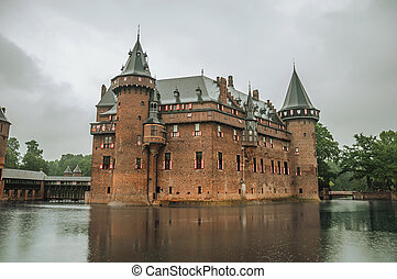 De Haar Castle facade with ornate brick towers and water moat on rainy day, near Utrecht.