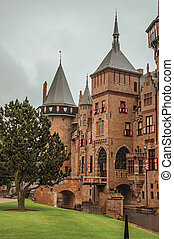 De Haar Castle with brick towers, water moat and lawn garden on rainy day, near Utrecht.