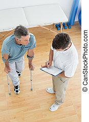 de hoge mening van de hoek, van, een, mannelijke , therapist, het bespreken, rapporten, met, een, invalide, patiënt, in de gymnastiek, op, ziekenhuis