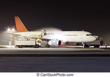 De-icing od plane - White plane with red tail during...