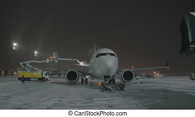 De-icing tail wings of the airplane before night departure -...