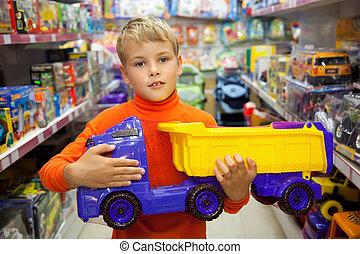 de, jongen, in, winkel, met, stuk speelgoed vrachtwagen, in, handen