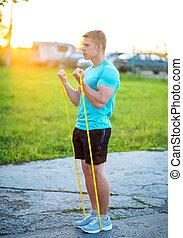 de, kerel, pompen, de, spierballen, van, de, biceps, in, de, avond, joint, exercises., zomer, levensstijl, motivatie, is, strong., een, man, in het park, kneads, spierballen, voor, training., gezonde , lifestyle.