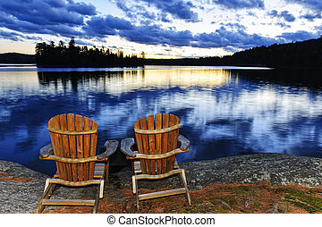 de madera, sillas, en, ocaso, en, orilla de lago