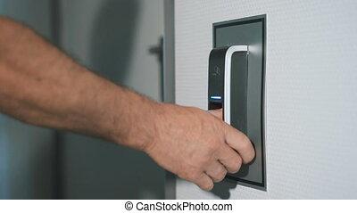 de, man, zet, zijn, pulken op, een, fingerprint scanner, welke, is, ontworpen, binnengaan, de, door., moderne, veiligheid, technologie, in, alledaags, leven, van, employees., werken, van, bescherming, tegen, inbraak, afsluiten, boven.