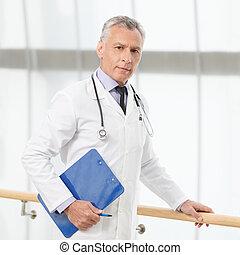 de, meest, begaafd, en, professioneel, arts., zeker, mondige arts, staand, met, een, klembord, en, kijken naar van fototoestel