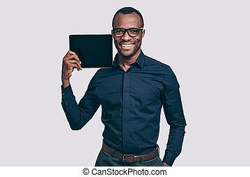 de ruimte van het exemplaar, op, zijn, tablet., mooi, jonge, afrikaanse man, verdragend, digitaal tablet, op, zijn, schouder, en, het glimlachen, terwijl, staand, tegen, grijze , achtergrond