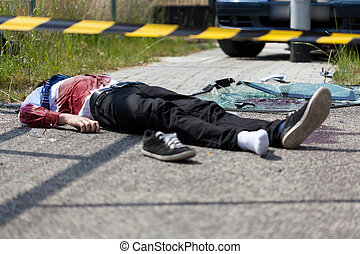 Dead casualty after a car crash - A dead man lying on the...