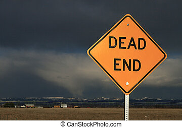 A dead end sign with ominous looking clouds in the distance.