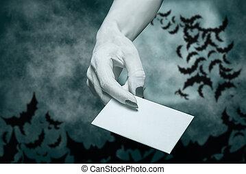 Dead hand giving blank card in Halloween night.