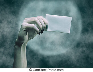Dead hand holding blank copy-space white card in Halloween.