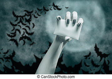 Dead hand with blank card in Halloween dark night, copy-space.