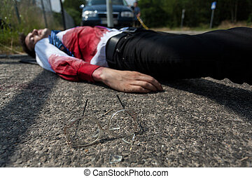 Dead man in bloody shirt lying on the street