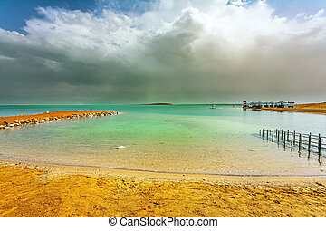 Dead Sea. Israel. Magnificent exotic resort for treatment and relaxation. Convenient gangway for descending into the water. Gloomy sky with dark thunderclouds.