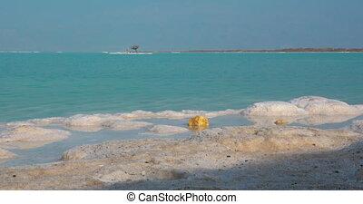 Dead Sea skyline scene with salty beach and islets, Israel -...