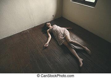 Dead woman lying on the wooden floor. Empty room