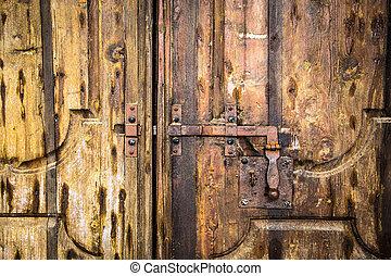 Deadbolt on wooden door. - Iron rusty deadbolt on old wooden...