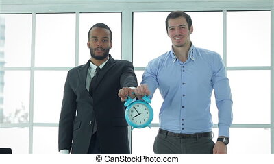 Businessmen are holding big clock alarm clock