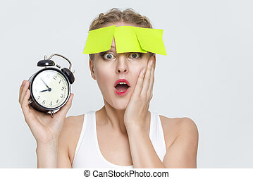 Deadline Concept. Portrait of Surprised and Stressed Caucasian Female With Alarm Clock And Empty Stickers on Forehead.