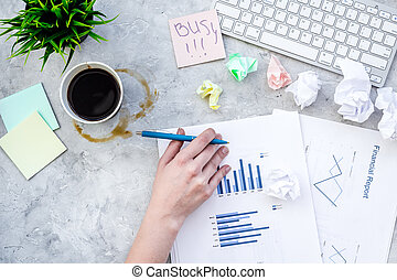 Deadline in office. Sticker Busy on desk covered with crumpled paper and stationery near sheet with chart on grey background top view