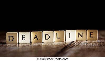 Deadline word made of tiles on dark wooden background
