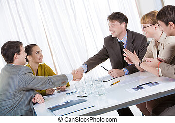 Image of confident partners shaking hands while their colleagues congratulating them