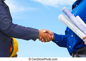 Deal on construction plan - Two contractors shake hands with...