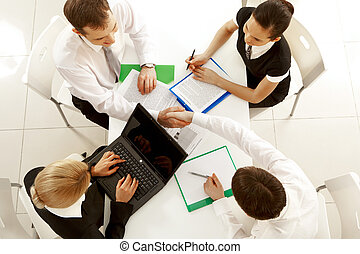 Deal - View from above of happy partners shaking hands at...