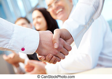 Deal - Image of business handshake after signing new...