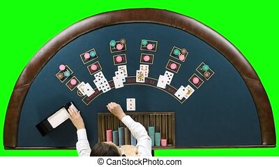 Dealer at the poker table lays chips under the game of poker. Green screen. Top view