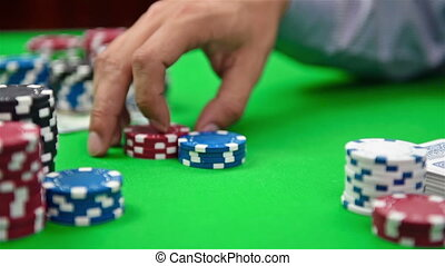 dealer collects poker chips from the table