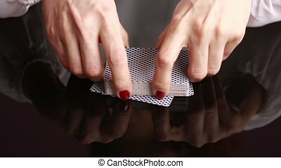 dealer handling playing cards at a poker table. Black background